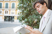 Attractive young businessman reading the newspaper while sitting in the city with classic office buildings around him. — Stock Photo
