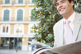Close up portrait of an attractive businessman with an open newspaper in the city, smiling. — Stock Photo
