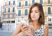 Young attractive businesswoman using a cell phone in a classic city. — Stock Photo