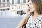 Close up portrait of a young businesswoman using a cell phone in the city — Stock Photo