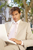 Attractive businessman sitting on a wooden bench in a classic city using a laptop computer. — Stock Photo