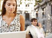 Podnikatel a podnikatelka pomocí technologie při posezení na dřevěných lavicích v klasické městské náměstí. — Stock fotografie