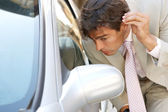 Attractive young businessman grooming using a car's reversing mirror to tidy his hair up. — Stock Photo