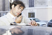 Portait of a young businessman using a cell phone and taking notes, leaning on a car in the city. — Stock Photo