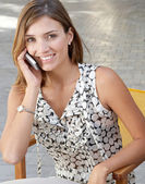 Businesswoman making a phone call while sitting on a chair at a coffee terrace outdoors. — Stock Photo