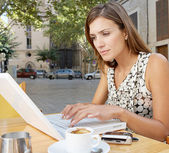 Businesswoman using a laptop computer while having a coffee in a coffee shop terrace — Stock Photo