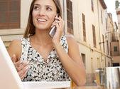 Empresária, fazendo uma ligação e usando um computador portátil enquanto tomando um café no terreiro de café — Fotografia Stock