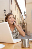 コーヒー ショップに座っている間携帯電話そしてラップトップ コンピューターを使用して実業家 — ストック写真
