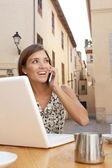 坐在咖啡厅里使用一部手机和一台便携式计算机的女商人 — 图库照片