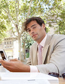 Young businessman using a cell phone while sitting in a coffee shop terrace table. — Stock Photo