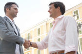 Two businessmen shaking hands while standing in front of a classic European building — Stock Photo