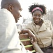 Young african american couple sitting on a bench in a park in the city of London. — Stockfoto