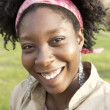 Close up portrait of an african american woman smiling happily at camera. - Stock Photo