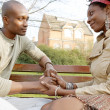 Fashionable couple holding hands while sitting on a wooden bench in a park in the city. — Stock Photo