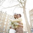 Young black couple hugging in a park at sunset, while visiting London city. — Stock Photo