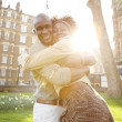 Young black tousits couple passionately hugging in a park, laughing and having fun. — Stock Photo