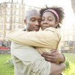 Young couple hugging each other in the city at sunset, smiling. - Stock Photo