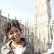 Young black woman tourist visiting Big Ben in London with a blue sky. — Stock Photo