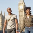 Attractive black tourist couple holding hands and walking past Big Ben while visiting London city on vacation. — Stock Photo #20082461