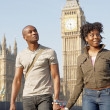 Attractive black tourist couple holding hands and walking past Big Ben while visiting London city on vacation. — Stock Photo