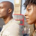 Attractive black tourist couple walking past Big Ben — Stock Photo
