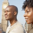 Attractive black tourist couple walking past Big Ben while visiting London city on vacation — Stock Photo