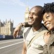 Stock Photo: Young tourist couple visiting London's Big Ben, smiling.