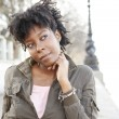 Attractive african american woman leaning on the river Thames' south bank — Stock Photo