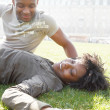 African american couple talking as they relax laying down on green grass — Stok fotoğraf
