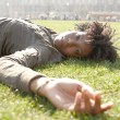 Attractive young black woman laying down on green grass in the city of London on a sunny day — Stock Photo