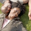 Over head view of an attractive black couple laying down on green grass — Stock Photo