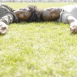 Stock Photo: African american couple laying down on green grass in the city.