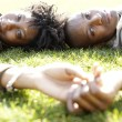 Close up portrait of a young african american couple laying down on green grass in the city — Stock Photo #20082633