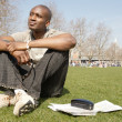 Young black tourist man sitting down on green grass in the city of London while visiting — Stok fotoğraf