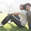 Young african american couple sitting back to back while visiting London on vacation — Foto Stock