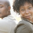Young attractive african american couple sitting back to back in a city park while on vacation — Stock Photo