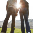 Rear view of a man and woman's figures holding hands while walking through London city on a sunny day. — Stock Photo
