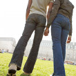 Rear view of figures of a man and woman holding hands while walking through London city on a sunny day. — Stock Photo