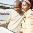 Black couple looking at a guide map on vacation — Stock Photo #20082855