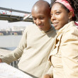 Black couple looking at a guide map on vacation - Stock Photo