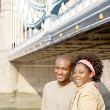 Attractive african american couple walking passed Tower Bridge in London — ストック写真