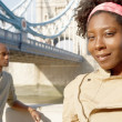 Foto Stock: Portrait of an african american man and woman standing by Tower Bridge