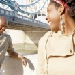 Portrait of an african american man and woman standing by Tower Bridge — Stok fotoğraf