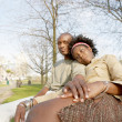 Young attractive black couple sitting down on a bench in the park — Stock Photo #20082987