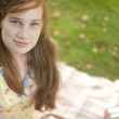 Stock Photo: Red hair teenager smiling at camerwhile sitting on blanket in forest.