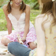 Two teenage girls having a picnic in the park. - Stock Photo