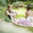 Stock Photo: Two teenage girls having a picnic in the park.