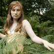 Teenage girl walking through forest fern leaves. - Stock Photo