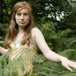 Teenage girl walking through forest fern leaves. — Stock Photo #20083149