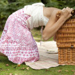 Teenage girl looking into a picnic basket in the forest. - Stock Photo
